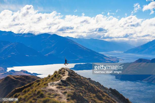 the strenuous yet highly rewarding hike to roy's peak in wanaka. the hike is difficult but the views are spectacular. people stop at this mountain peak to take this famous photograph. a man jumps in excitement after reaching the peak. - matthew hale stock pictures, royalty-free photos & images