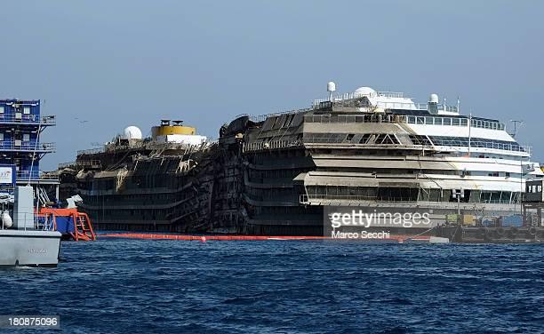 The stricken Costa Concordia is seen upright after the parbuckling operation was succesfully completed around 4 am on September 17 2013 in Isola del...