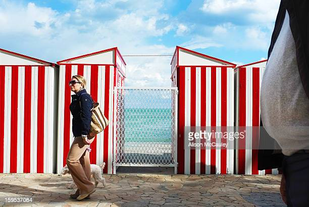 The striped red and white beach huts are set against a blue and fluffy white clouded sky. The turquoise sea can be seen between the huts. A young...