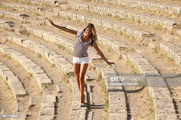 The Striscia la Notizia velina Costanza Caracciolo walking and balancing on the steps of the Ancient Theatre of Taormina during a photo shooting...