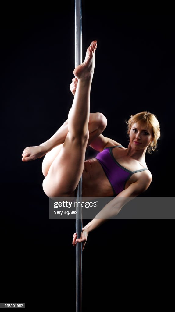 The strong and graceful young girl performing acrobatic exercises on pylon : Foto stock