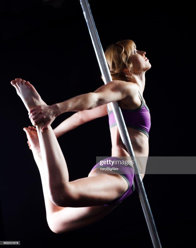 Das starke und anmutige junge Mädchen Durchführung akrobatische Übungen am pylon : Stock-Foto