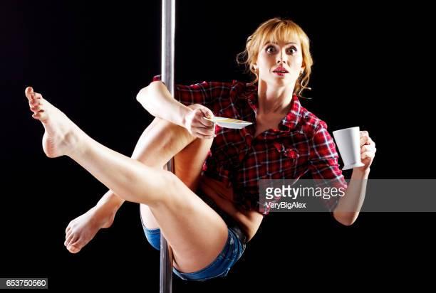 La jeune fille forte et gracieuse, effectuant des exercices acrobatiques sur pylône