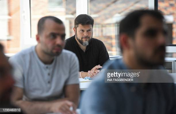 The student Ender Cetin listens during a lesson in the classroom of the Islamkolleg Deutschland in Osnabrueck, western Germany on June 14, 2021. -...