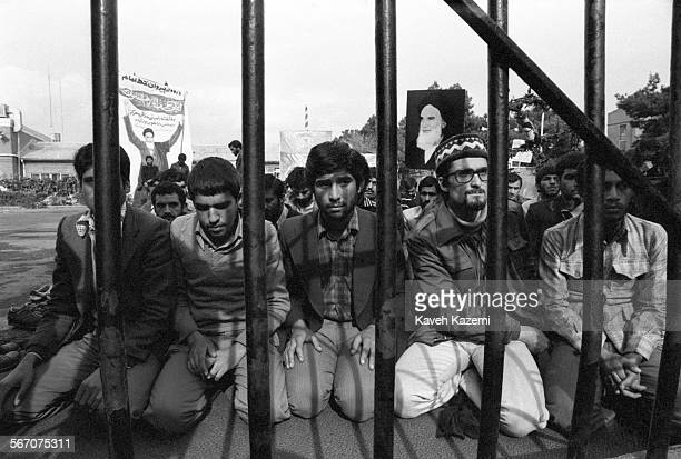 The 'Students Following The Imam Khomeini Line' who hold the American hostages captive inside the compound seen during prayers on the compound behind...