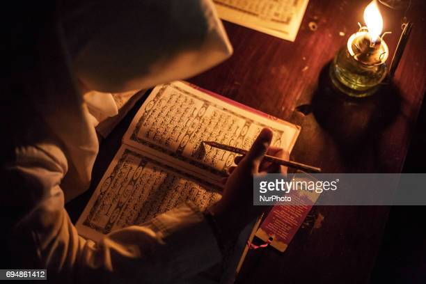 The students of Baitul Mustafa Islamic Boarding School reading the Holy Quran using the oil lamps lighting to celebrate the holy day of Nuzulul Quran...