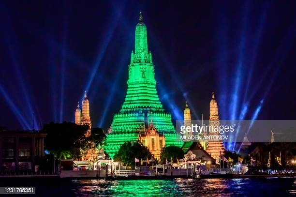The stupa of the Buddhist temple Wat Arun is illuminated in green to mark St. Patrick's Day in Bangkok on March 17, 2021.