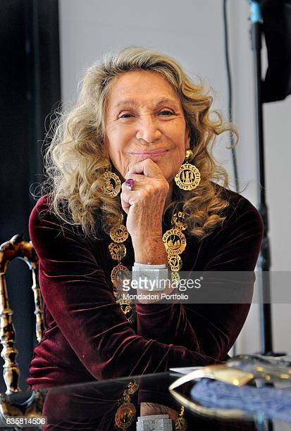 The style icon queen of high society and Italian painter Renato Guttuso's muse Marta Marzotto sitting and smiling with one hand on her chin at the...