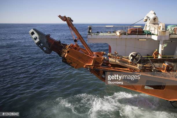 The suction arm of the 'crawler' tractor used to suck sediment from the seabed drops into the sea from the Mafuta diamond mining vessel operated by...