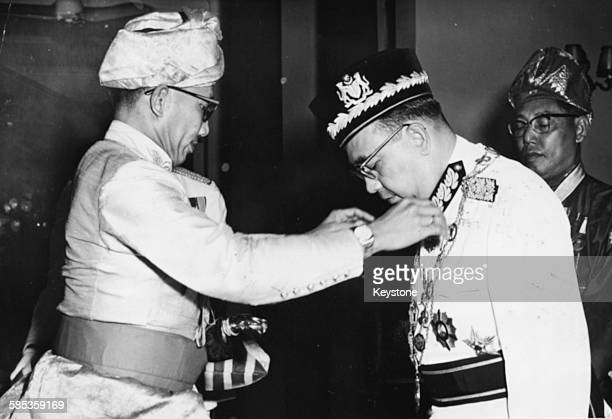 The Sultan of Brunei giving an investiture to Abdul Razak Hussein Prime Minister of Malaysia awarding him the Most Honorable Order of the Crown of...