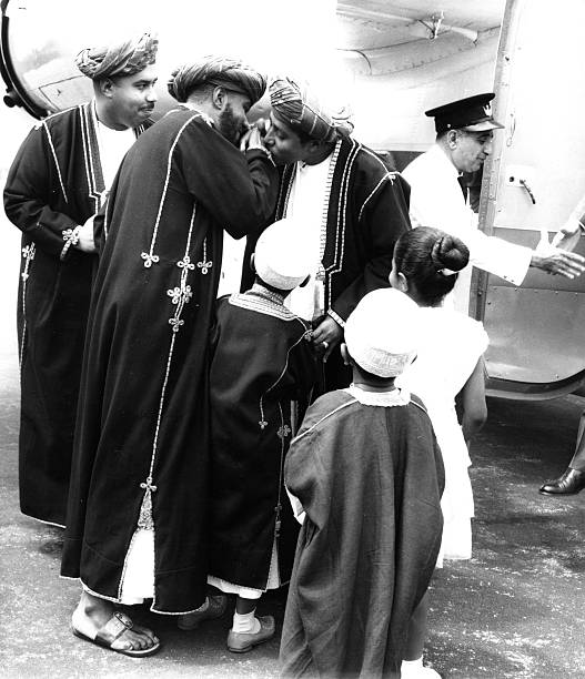 The Sultan of Zanzibar greets his youngest brother the bearded Prince Harub in the traditional way kissing him on the hand circa 1960 Looking on are...