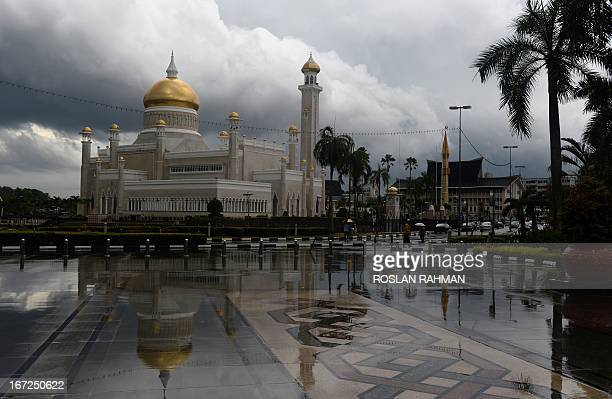 The Sultan Omar Ali Saifuddin Mosque is reflected in the pavement after heaving rains hit Bandar Seri Begawan on April 23 2013 a day before a meeting...