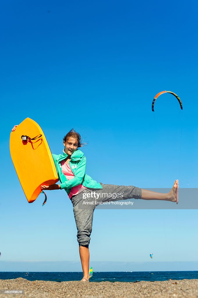 The summer is here! Happy cheerful teenage girl with surfboard : Stock Photo