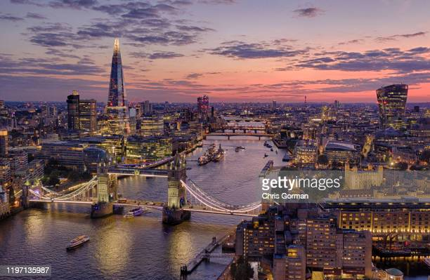 The summer sky sets behind the city of London on a Saturday night on July 13, 2019 in London, United Kingdom. Tower Bridge, The Tower of London and...