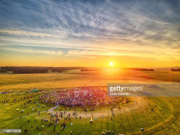 The summer solstice sun breaks through the stones at Stonehenge as observed by thousands of revellers on June 21 2019 in Amesbury United Kingdom