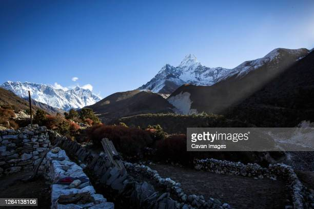 the summit of ama dablam looms over shadows of nepal's khumbu valley. - solu khumbu stock pictures, royalty-free photos & images
