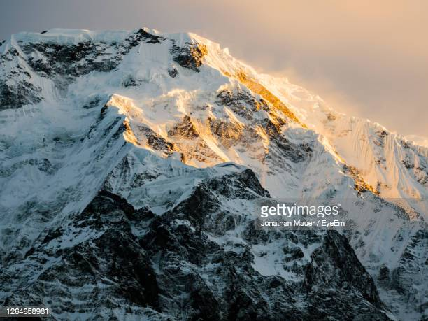 the summit of annapurna south at sunrise, sunlight shining on the snowcapped ridges on the peak. - annapurna south stock pictures, royalty-free photos & images