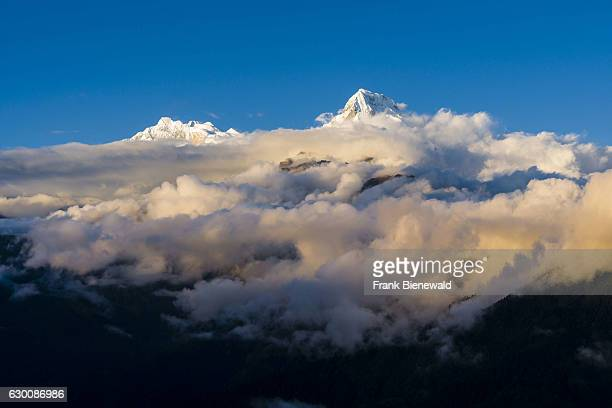 The summits of Annapurna 1 and Annapurna South are towering out of monsoon clouds at sunset, seen from Poon Hill.