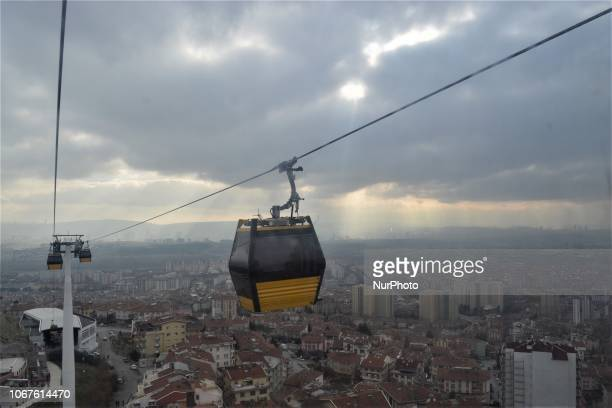The sun beams through dark clouds as cable cars move on the line between Yenimahalle and Sentepe districts in Ankara Turkey on December 2 2018 The...