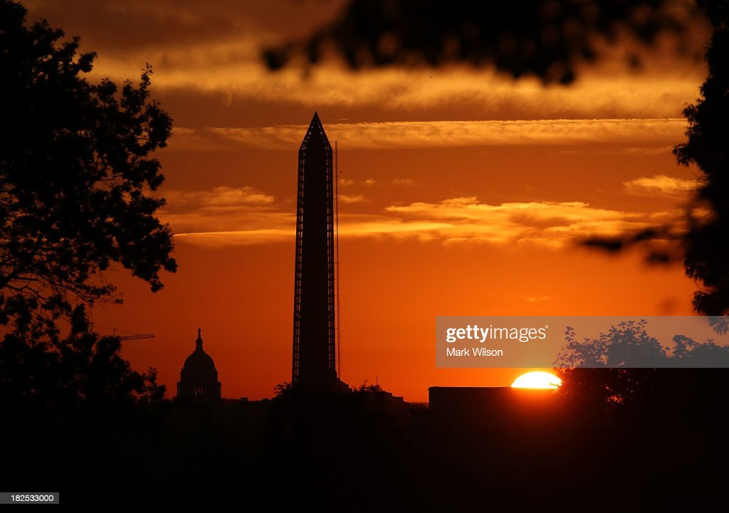 The sun begins to rise behind the U.S. Capitol and The Washington Monument, September 30, 2013 in Washington, DC. Negotiation's are ongoing in Congress between the House and Senate about funding the government to avoid a shutdown at midnight on October 1.