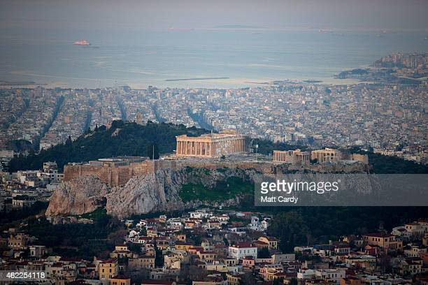 The sun begins to rise over Athens and the Acropolis seen from the summit of Mount Lycabettus following the electoral success by Syriza in the Greek...