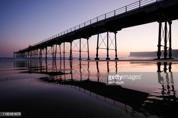 The sun begins to rise over Saltburn pier on February 27 2019 in Saltburn By The Sea England Another day of unseasonably warm weather is expected...