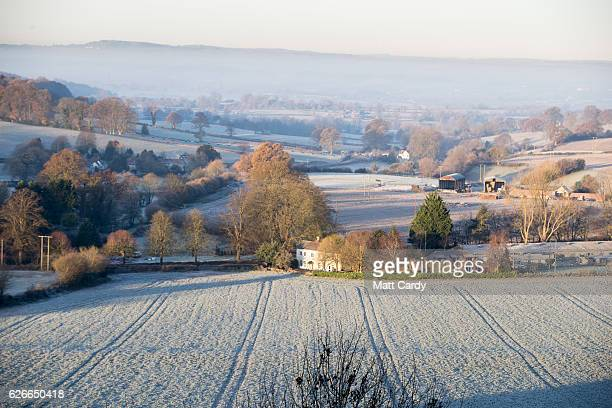 The sun begins to rise over Somerset and Wiltshire countryside viewed from the National Trust's Cley Hill as the country wakes up to subzero...