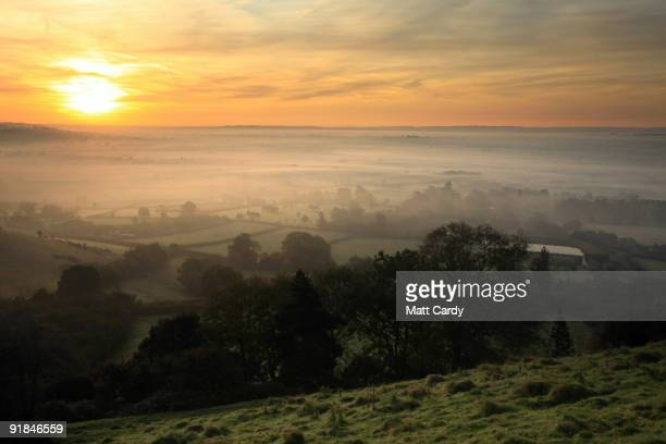 The sun begins to rise over the Somerset Levels looking towards Pilton on October 13 2009 near Glastonbury England England particularly in the south...