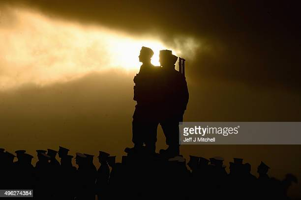 The sun breaks through the clouds behind a statue as both serving and former commandos gather during the Commando Memorial Service commemorate and...