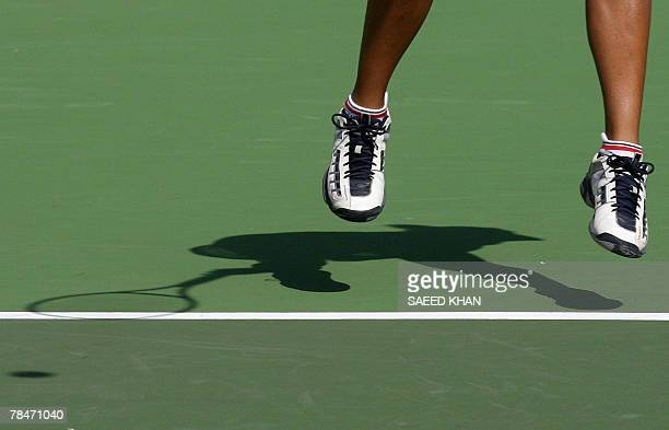 The sun casts a shadow of Thailand's Nudnida Luangnam as she serves Sandy Gumulya of Indonesia during the tennis women's final match at the 24th...