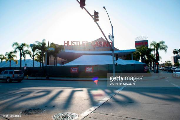 The sun casts the shadows of the Hustler Casino sign onto the road on February 10, 2021 in Gardena, a city the South Bay region of Los Angeles...