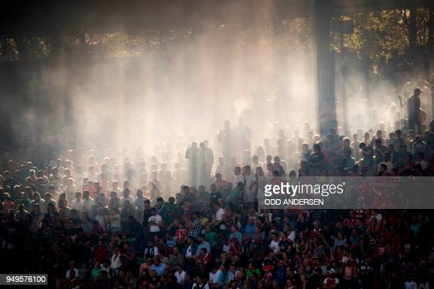TOPSHOT The sun cuts through the haze of flares hanging in the stand during the German first division Bundesliga football match between Hannover 96...