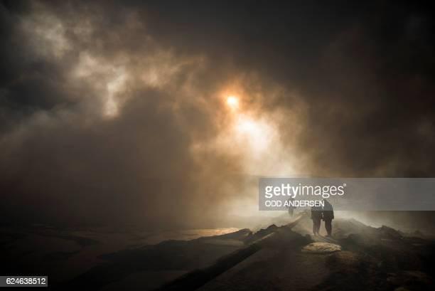 TOPSHOT The sun cuts through the smoke as workers tasked with putting out the fire in an oil well set ablaze by retreating Islamic State jihadists...