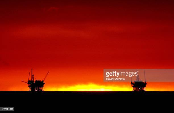 The sun fades from view as it sets between the Hillhouse A left and Hillhouse B oil and gas platforms near the Federal Ecological Reserve in the...