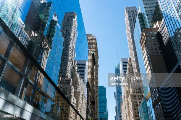 the sun illuminates the rows of high-rise buildings at 42nd street midtown manhattan new york city usa on jul. 30 2017. - jul photos et images de collection