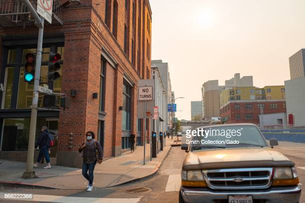 The sun is almost entirely obscured by smoke from the Napa wildfires as a woman wearing a pollution mask walks down Folsom Street in San Francisco...
