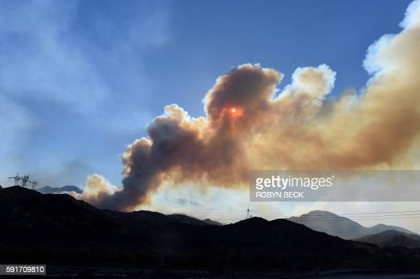 TOPSHOT The sun is obscured by a long plume of smoke from the Blue Cut Fire near Wrightwood on August 17 2016 An inferno scorching swaths of southern...