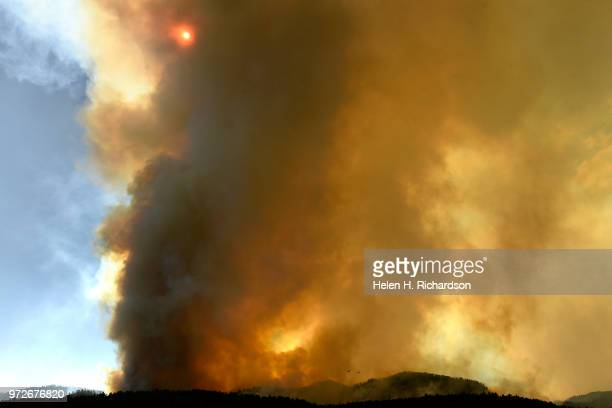 The sun is obscured by the large plume of the 416 fire as it continues to burn in the San Juan National Forest on June 12 2018 in Hermosa Colorado...