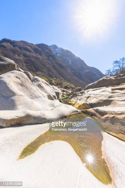 The sun is reflected in a puddle in the Verzasca River, Lavertezzo, Verzasca Valley, Canton of Ticino, Switzerland, Italy.