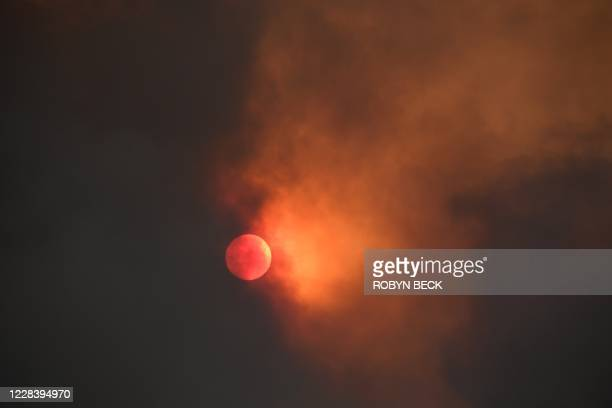 The sun is seen behind smoke from the Bobcat fire rising above in the Angeles National Forest above Duarte, California, about 27 miles northeast of...