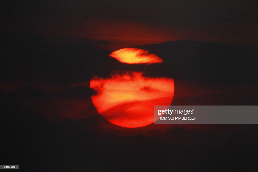 The sun is seen in red as it sets over t : Nieuwsfoto's