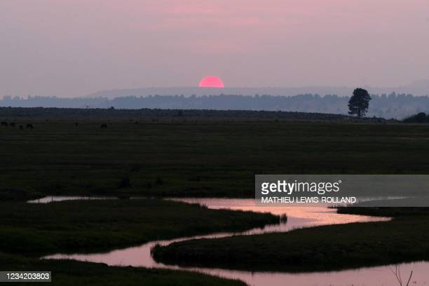 """The sun is seen setting amid thick wildfire smoke from the Bootleg Fire on July 25, 2021 near Bly, Oregon. - The """"Bootleg Fire"""" in Oregon, which..."""