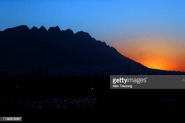 The sun is seen setting behind the mountain during the game between the St Louis Cardinals and the Cincinnati Reds at Estadio de Beisbol Monterrey on...
