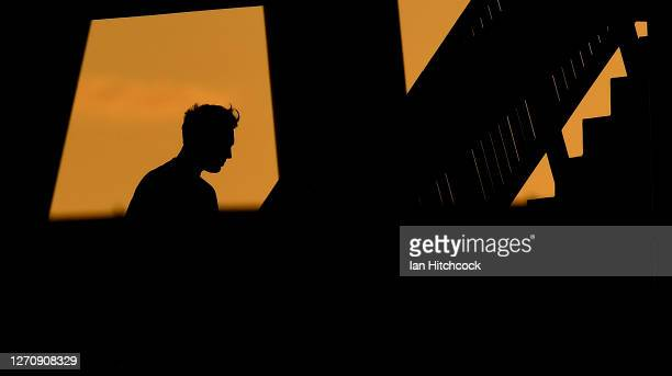 The sun is seen setting behind the western grandstand as a supporter looks for his seat before the start of the round 17 NRL match between the North...