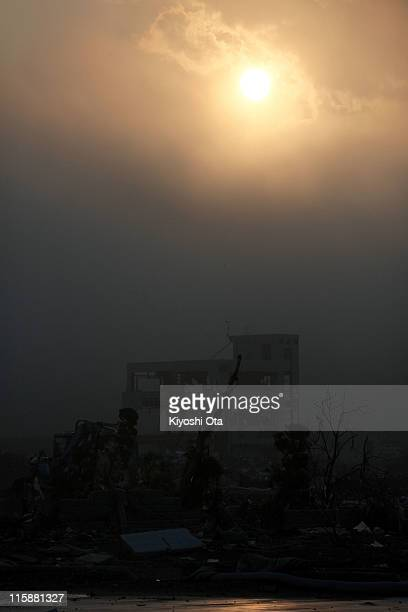 The sun is to set over the destroyed town on June 11 2011 in Minamisanriku Miyagi Japan Japanese government has been struggling to deal with the...