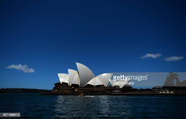 The sun light reflects on the sails of Sydney's iconic land mark Opera House as a water taxi passes by on December 18 2013 Australia's central bank...