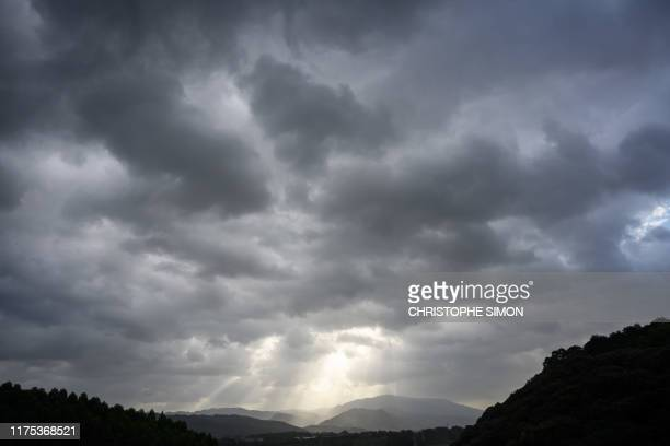 The sun peaks out from behind a band of dark clouds between Oita and Fukuoka on southern Kyushu island on October 12 as powerful Typhoon Hagibis...
