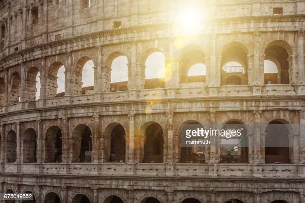 The sun peeking through the arches of the Colosseum in Rome