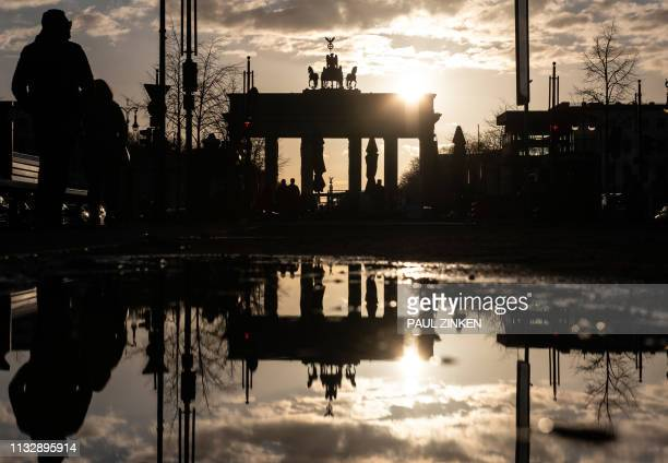 TOPSHOT The sun reflects in a puddle as it sets behind Berlin's landmark the Brandenburg Gate on March 25 2019 / Germany OUT