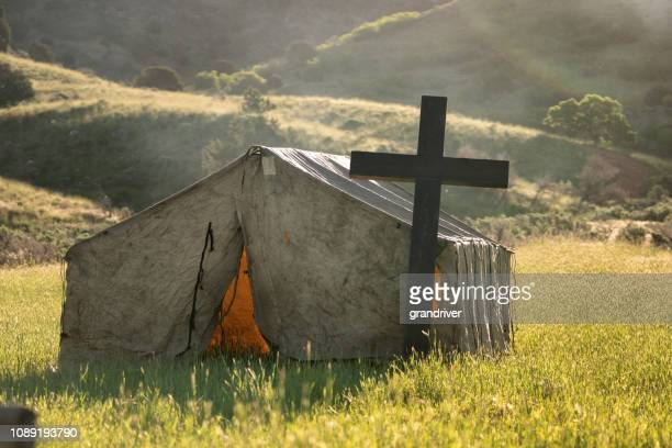 the sun rise behind a christian tent chapel out in a field for cowboys to attend - religious service stock pictures, royalty-free photos & images
